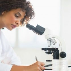 young woman working with a microscope in a science laboratory