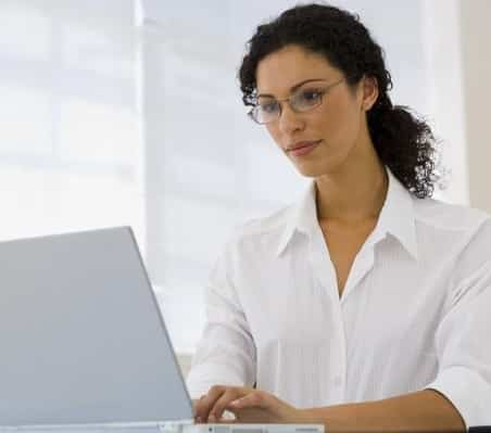 woman typing on laptop wearing white collared blouse and glasses