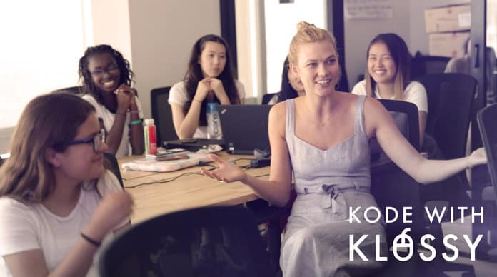 Karlie Kloss posing with young diverse girls in a classroom setting