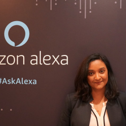 Amazom's Miriam Daniel smiling and standing in front of a poster for Amazon Alexa