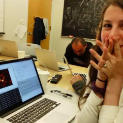 Katie Bouman sitting at her computer with a smile on her face and hands up to her mouth in excitement