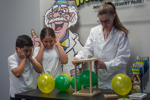 STEM teacher showing two grade school children a nail and balloon experiment