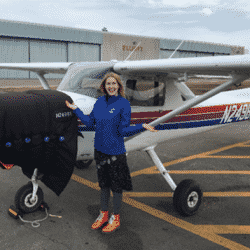 Astronaut Abby posing next to her plane she pilots