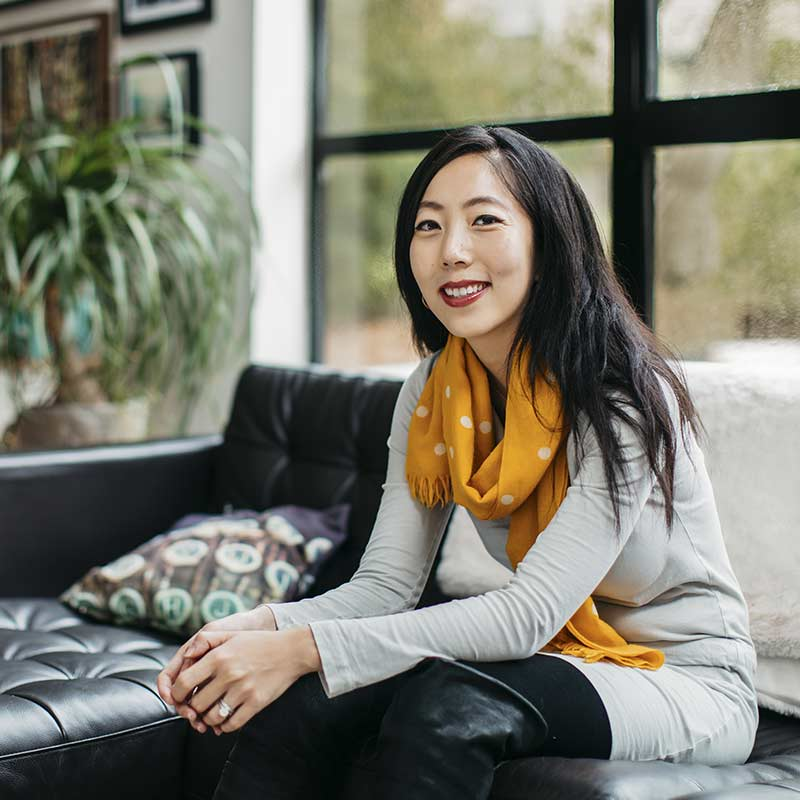 Julie Zhuo VP of Facebook poses seated on couch wearing an off white sweater and a mustard colored scarf