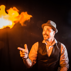 WonderWorks magician using flamethrower props on stage at dinner show