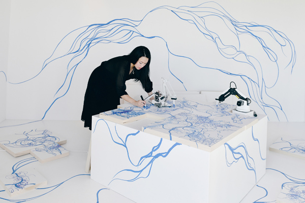 Sougwen is painting on a canvas draped table with a small robot on the table