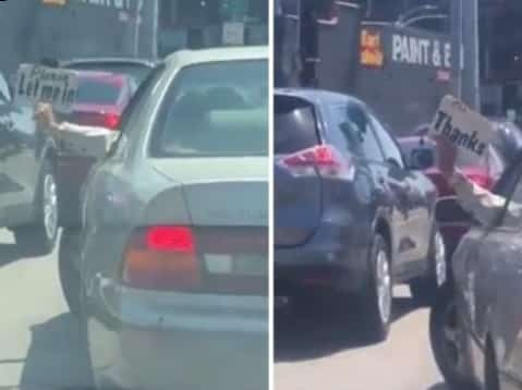 driver holding signs outside car window in heavy traffic