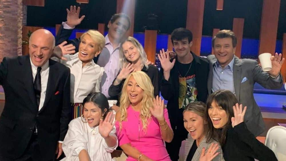 Selena Gomez poses with the Shark Tank cast smiling and waving her hand