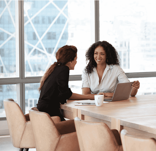 women talking together at conference table