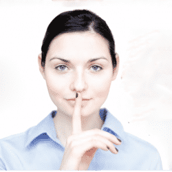 professional woman holding her finger over her mouth as a hush signal