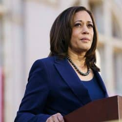 Kamala Harris dressed in a blue suit stands at podium giving a speech