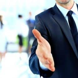 man extending his hand wearing a suit with business people in the background