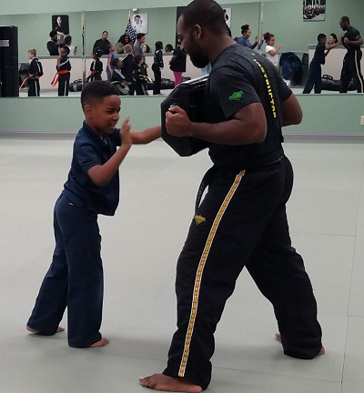 Coach and young student practicing self-defense with a punching bag
