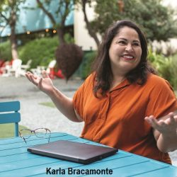 Karla Bracamonte siting outside at a table with a laptop