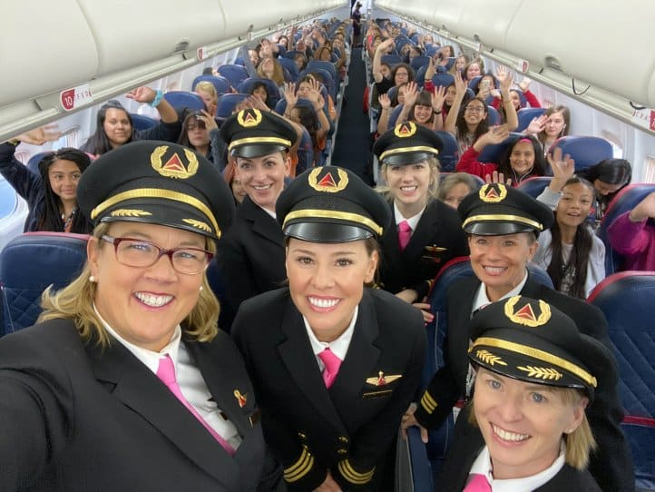 Delta flight crew pose with students in cabin of plane