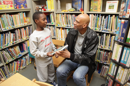 Kareem out in community visiting with a young boy in the library