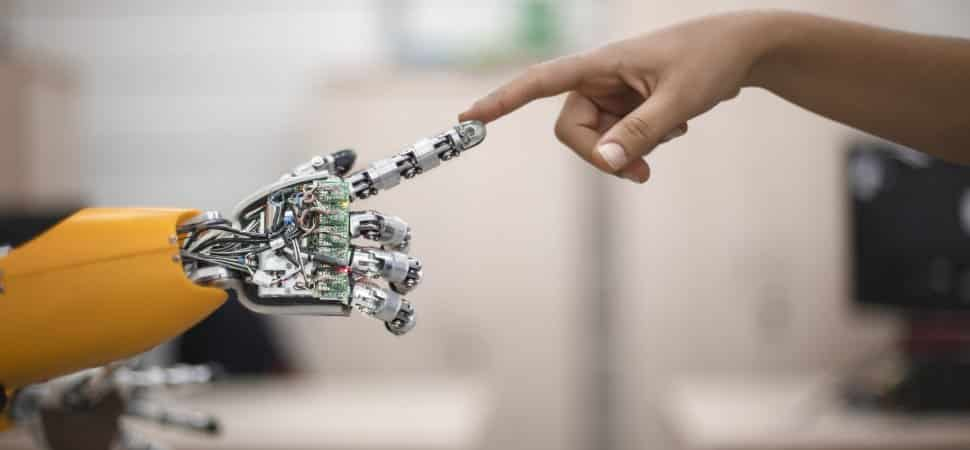 pictured is a human hand touching a robotic hand
