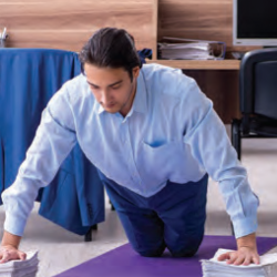 Athletic man doing pushups in office on the floor with two large stacks of pater under his hands