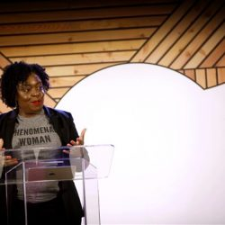 Kimberly Bryant stands behind a podium wearing a shirt that read Phenomenal Woman