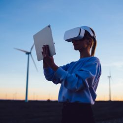 Young woman engineer wearing VR headset making calculations using touchpad program and stylus while standing on background of evening sky and windmills in countryside