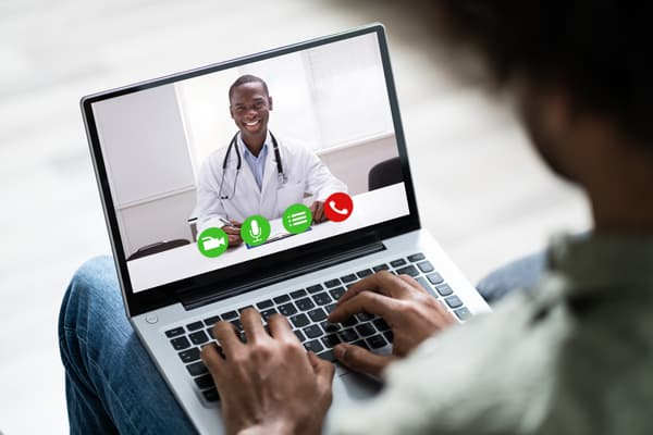 Close-up Of A Man Using Laptop To Communicate With Doctor