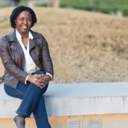 Fatim Mbaye pictured sitting on short wall outside of her Qualcomm office