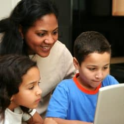 Mom and her two children in the kitchen on the computer