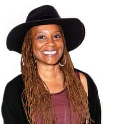 Tracy Gray is pictured wearing a broad brimmed black hat and smiling
