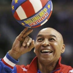 Pat Williams aka Curly wearing HArlem Globetrotter uniform, smiling, spinning basketball on fingertips