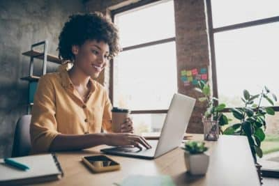 black woman on computer coffee in hand at home