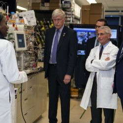 black woman scientist stands next to equipment in lab talking with President Trump Dr. Farci and others