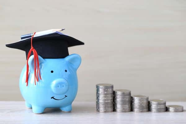 A blue piggy bank wearing a graduation cap with stacks of coins next to it.