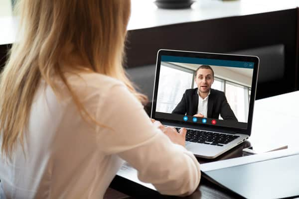 woman interviewing with man on website, close up, rear view