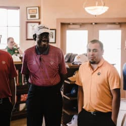 Golf Pros stand together in pro shop smiling