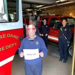 man holding donated face shields at fire station