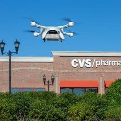 A drone holding a small UPS package flies in front of a CVS Pharmacy